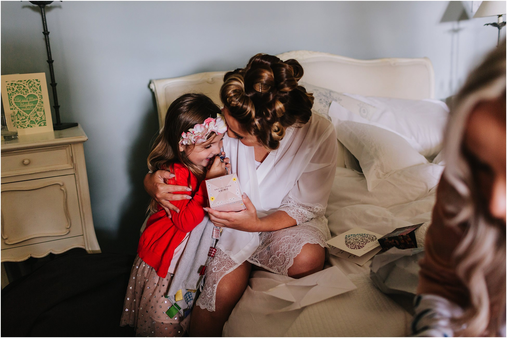 Bride and flower girl hug