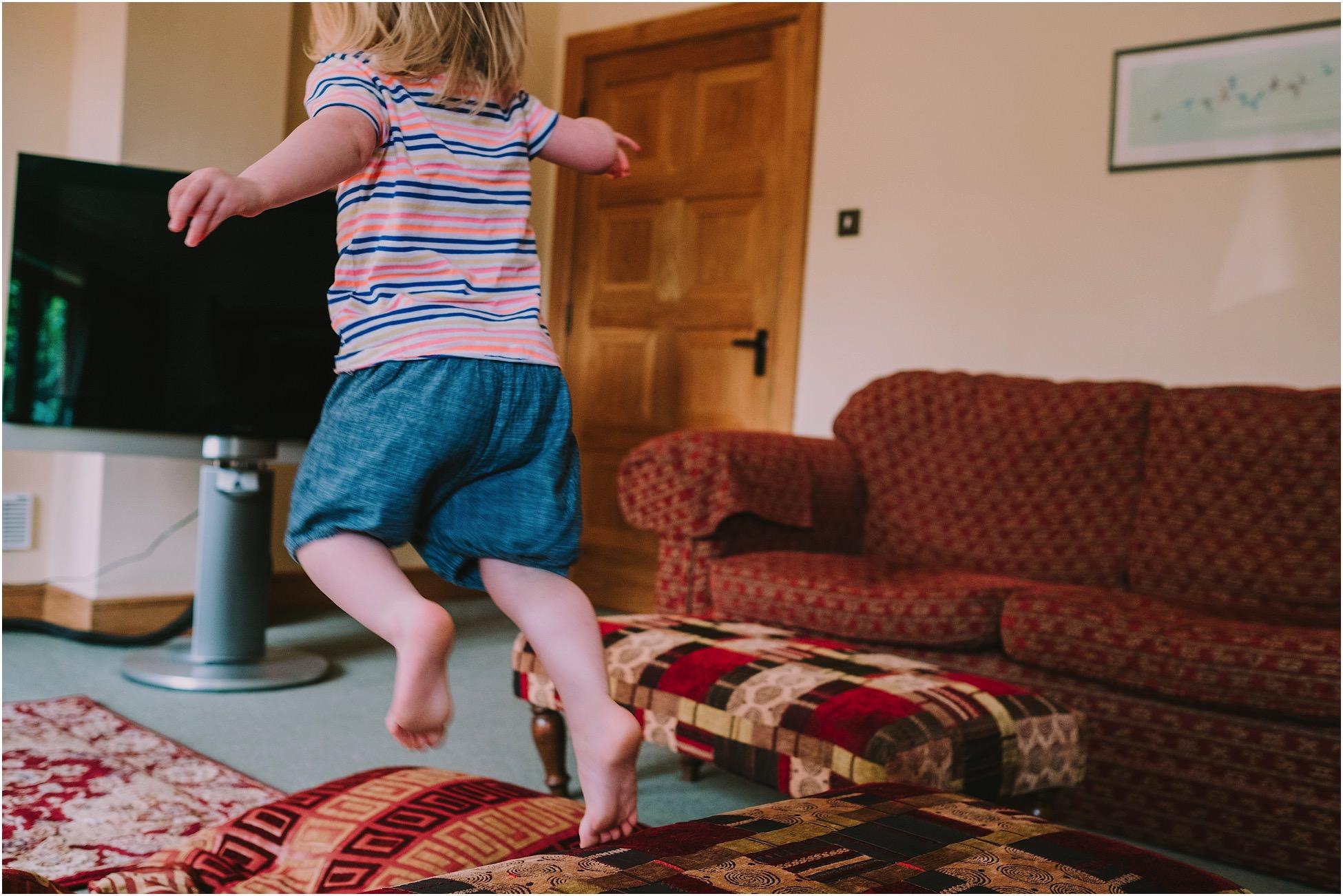 Little flower girl jumping off a sofa