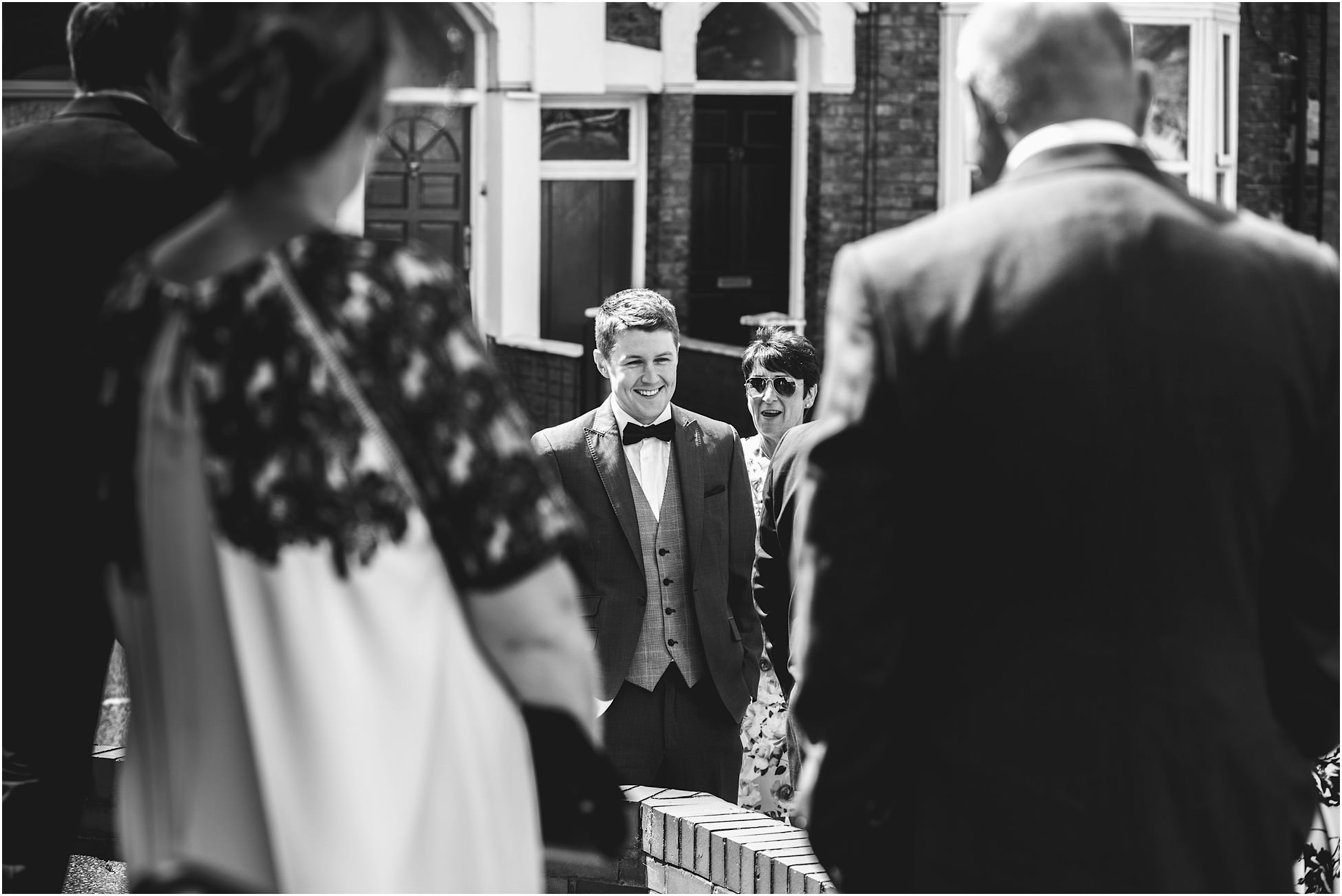 Groom outside church with guests at his Cheshire wedding