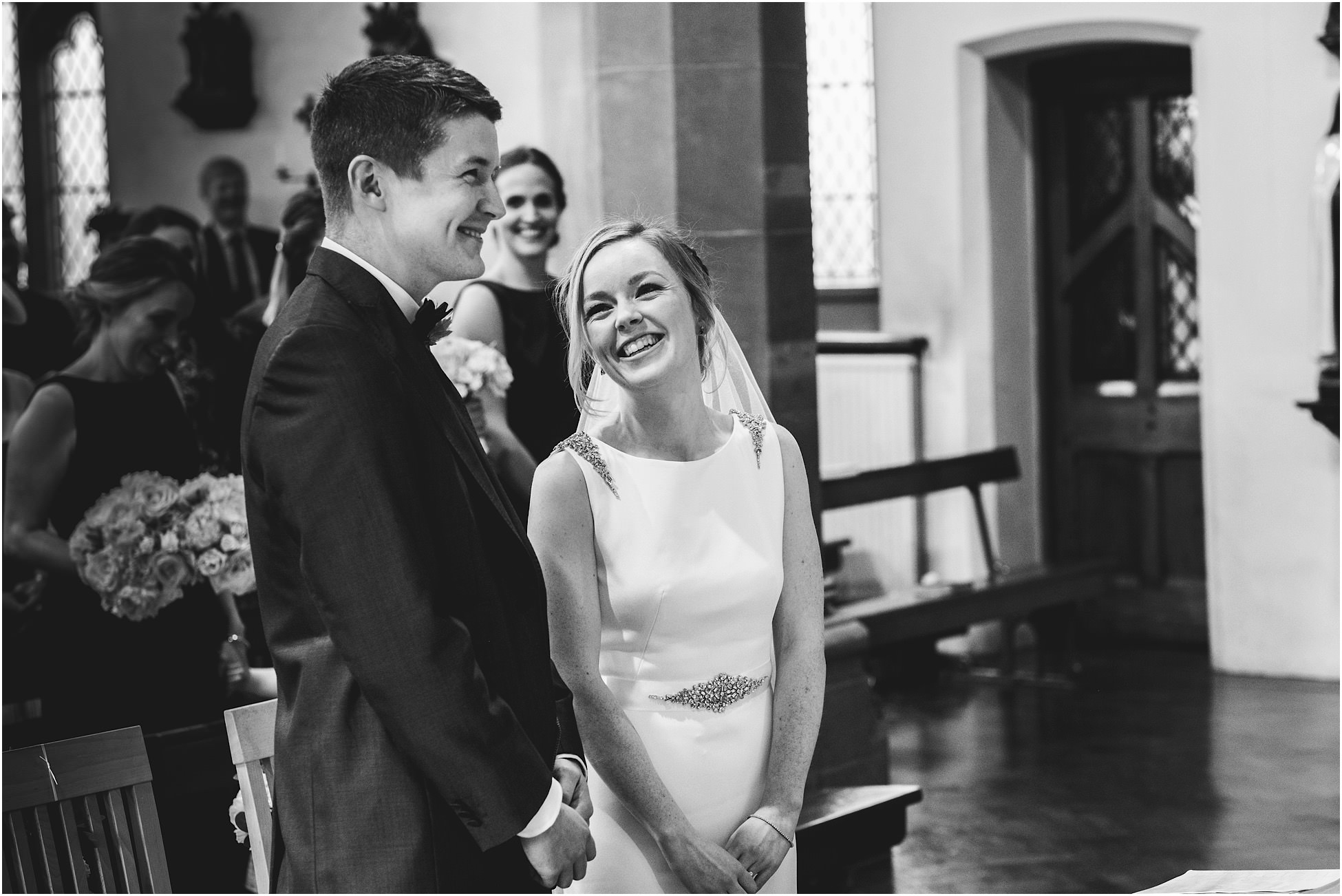 Black and white image of bride and groom stood in church