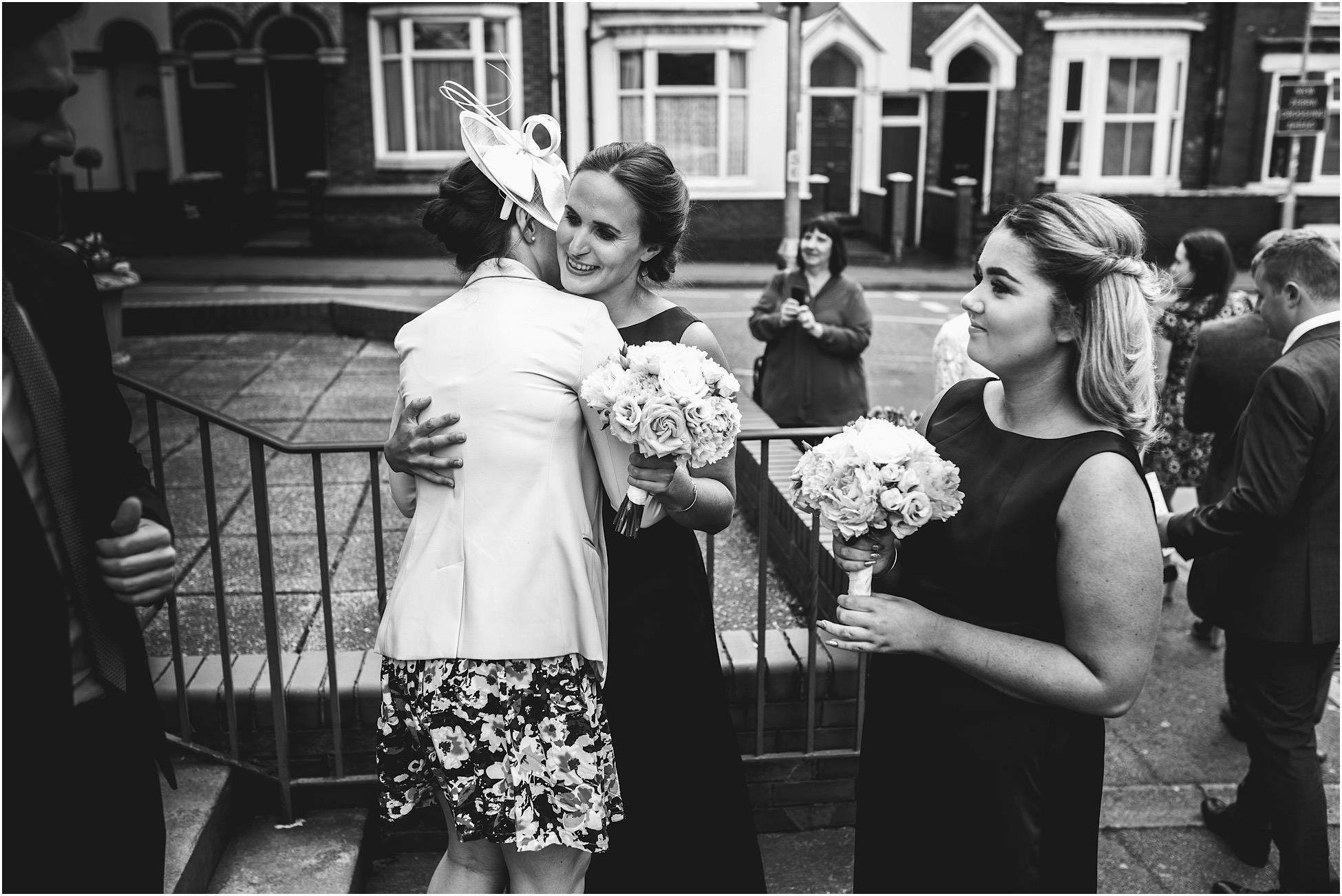 Bridesmaid hugging wedding guest outside church