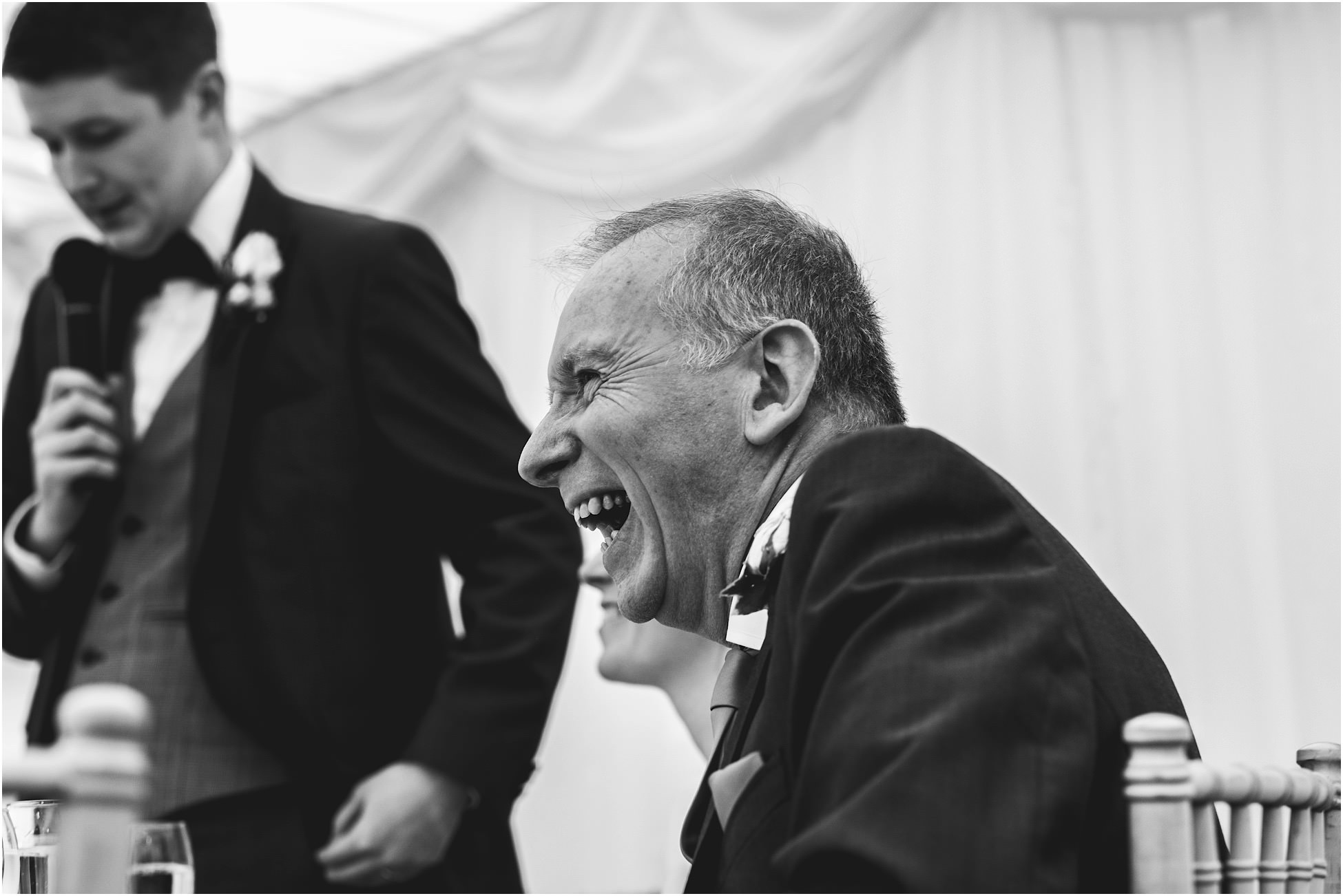 Father of the bride laughing during wedding speeches