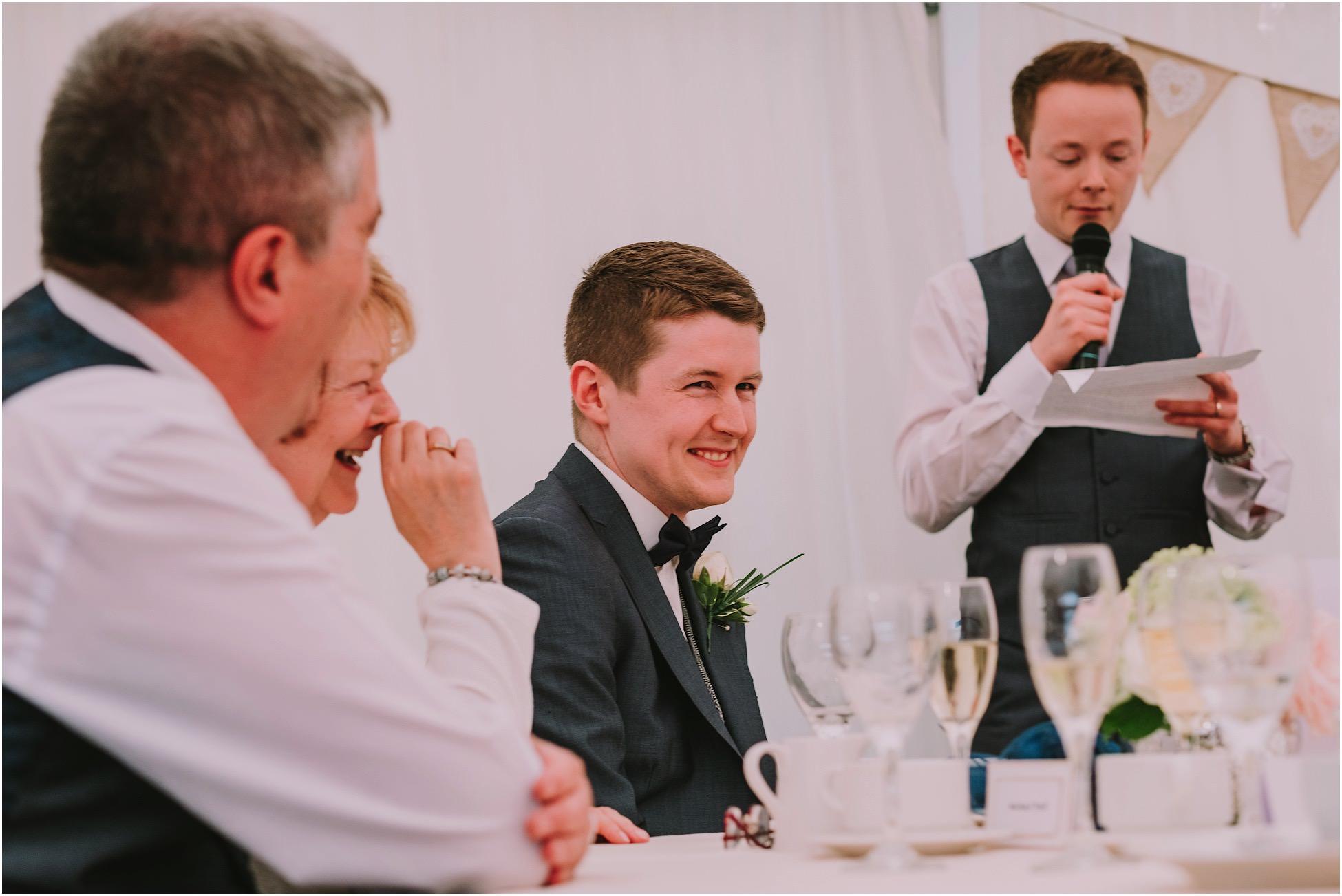 Groom grimacing during his Best Man's speech